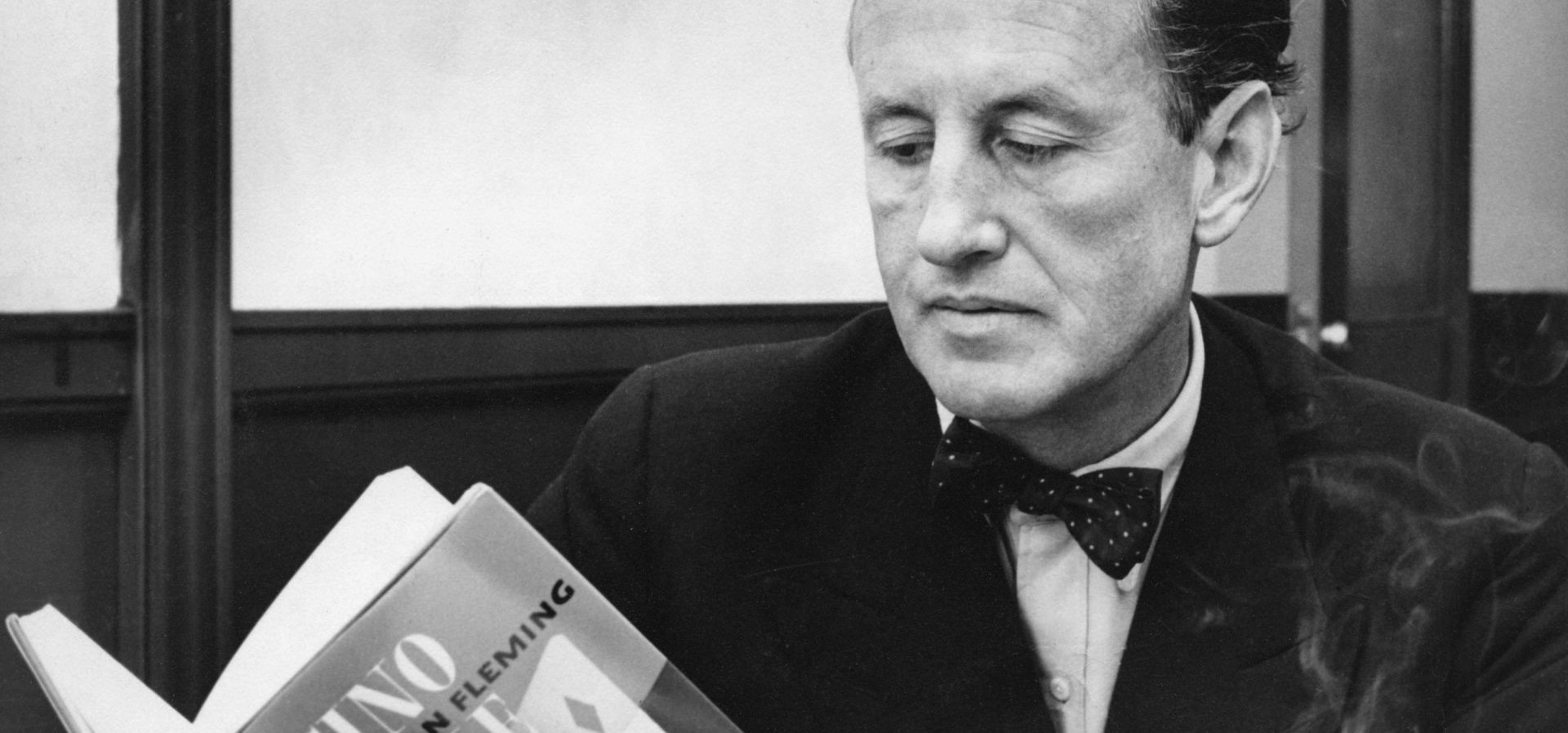 Ian Fleming reading a copy of Casino Royale