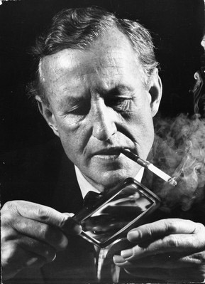 Ian Fleming looking at Brazilian pirate coins with a magnifying glass, 1962